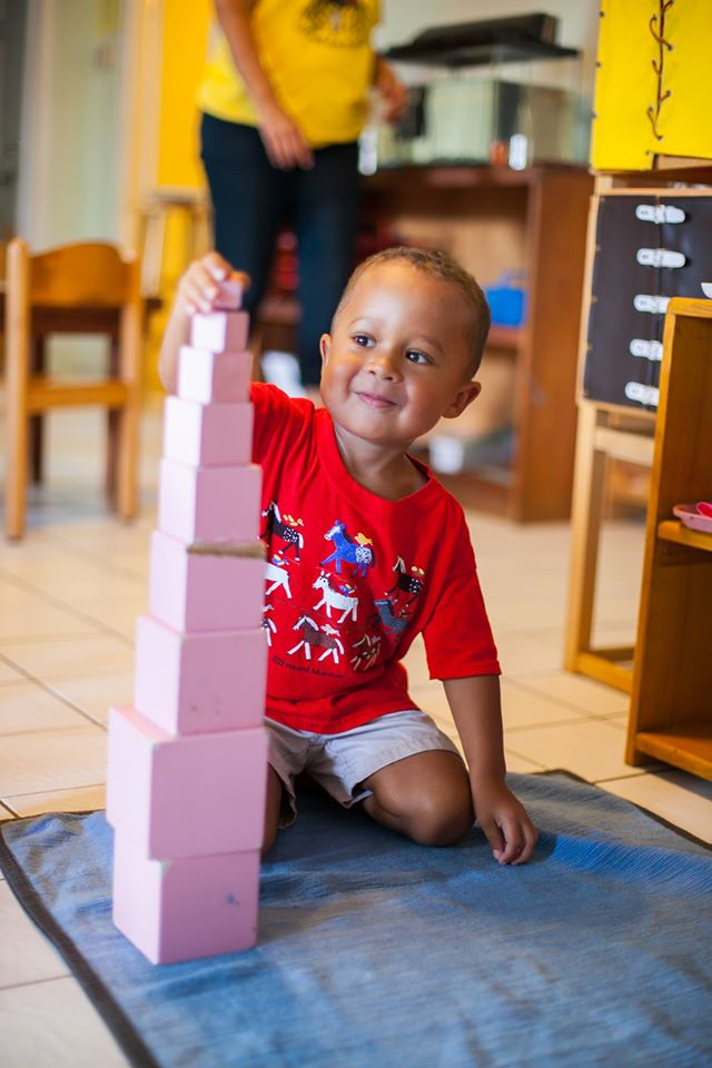 A preschooler assembles a tower of pink wooden cubes in subtly graduated sizes.